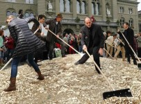 "Committee members use brooms and shovels to spread out five cent coins over the Federal Square during an event organised by the Committee for the initiative ""CHF 2,500 monthly for everyone"" (Grundeinkommen) in Bern October 4, 2013. The Committee delivered 126,000 signatures to the Chancellery on Friday to propose a change in the constitution to implement their initiative. The initiative aims to have a minimum monthly disposal household income of CHF 2,500 (US$ 2,700) given by the government to every citizen living in Switzerland. REUTERS/Denis Balibouse (SWITZERLAND - Tags: POLITICS CIVIL UNREST)"