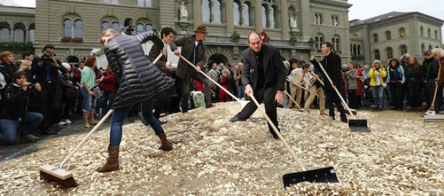 """Committee members use brooms and shovels to spread out five cent coins over the Federal Square during an event organised by the Committee for the initiative """"CHF 2,500 monthly for everyone"""" (Grundeinkommen) in Bern October 4, 2013. The Committee delivered 126,000 signatures to the Chancellery on Friday to propose a change in the constitution to implement their initiative. The initiative aims to have a minimum monthly disposal household income of CHF 2,500 (US$ 2,700) given by the government to every citizen living in Switzerland. REUTERS/Denis Balibouse (SWITZERLAND - Tags: POLITICS CIVIL UNREST)"""